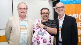 José Paulo Pereira, do Cond. Simas, com seu brinde, ao lado de Alberto Machado e do palestrante Sergio Simões